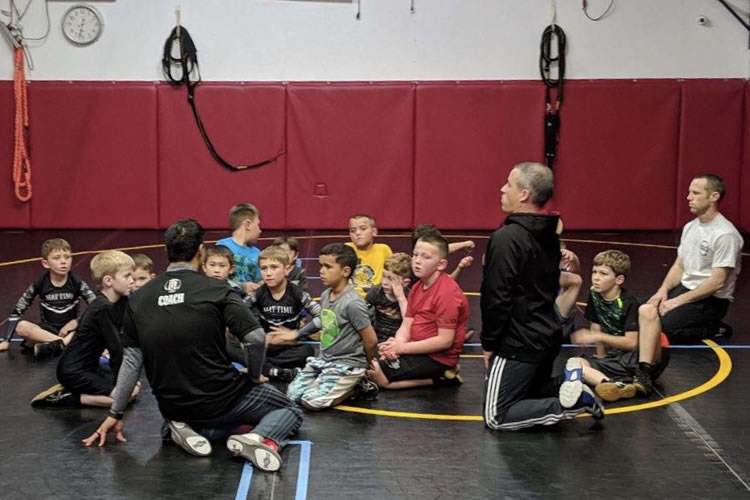 Coach Adrian talks to the kid wrestlers.